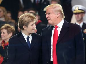 President Donald Trump stands with his son Barron Trump inside of the inaugural parade reviewing stand in front of the White House on January 20, 2017 in Washington, DC. Donald Trump was sworn in as the nation's 45th president today.