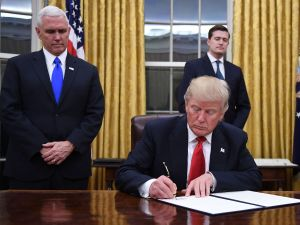 President Donald Trump signing an executive order in the Oval Office of the White House