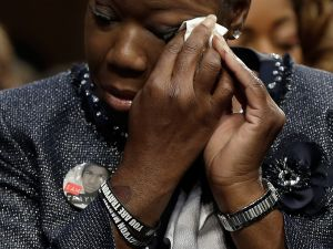 "Sybrina Fulton, mother of Trayvon Martin, wipes her eyes during a Senate Judiciary Committee hearing on ""Stand Your Ground"" laws October 29, 2013 in Washington, DC."