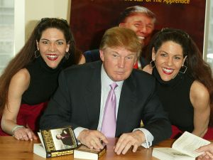 "NEW YORK - MARCH 24: Donald Trump poses for a picture with two fans while he signs copies of his new book ""How To Get Rich"" March 24, 2004 at Barnes and Noble in Lincoln Center in New York City. (Photo by Peter Kramer/Getty Images)"
