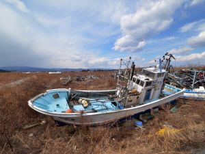 Fishing boats sit grounded on land years after the disaster in Namie, near the striken TEPCO Fukushima Dai-ichi nuclear plant in Fukushima prefecture on March 10, 2014, one day before the third anniversary of March 11 massive earthquake and tsunami.