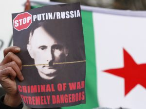 BERLIN, GERMANY - DECEMBER 07: A protester holds a placard showing a portrait of Russian President Vladimir Putin altered to look like Adolph Hitler during a demostration to demand an end to Russian aerial bombing of the Syrian city of Aleppo in front of the Russian Embassy on December 7, 2016 in Berlin, Germany. The Russian military is supporting Syrian government military forces fighting rebels in Aleppo with aerials bombardments that, according to independent observers, has resulted in the heavy loss of civilian lives.