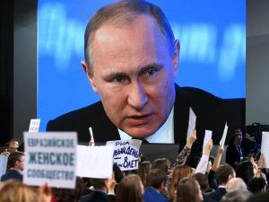 TOPSHOT - A video screen displays Russian President Vladimir Putin speaking during his annual press conference in Moscow while journalists hold the name of their media, on December 23, 2016. / AFP / Natalia KOLESNIKOVA (Photo credit should read