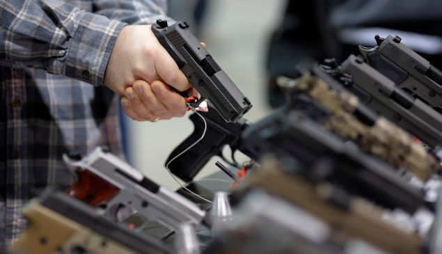 A visitor holds a pistol at a gun display during a National Rifle Association outdoor sports trade show on February 10, 2017 in Harrisburg, Pennsylvania. The Great American Outdoor Show, a nine day event celebrating hunting, fishing and outdoor traditions, features over 1,000 exhibitors ranging from shooting manufacturers to outfitters to fishing boats and RVs, and archery to art. / AFP / DOMINICK REUTER