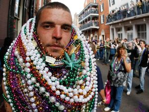 A reveler walks along Bourbon Street with a stack of beads around his neck during Mardi Gras day on February 24, 2009 in New Orleans, Louisiana.