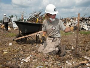 AmeriCorps volunteer Teri Jacobs picks up wood and debris from the remains of a home on June 18, 2011, in Joplin, Missouri. More than 28,000 volunteers went to Joplin to help clear debris in the weeks following a tornado.