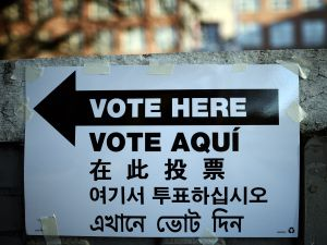 A directional sign in various languages is placed to point voters to a polling station in New York City.