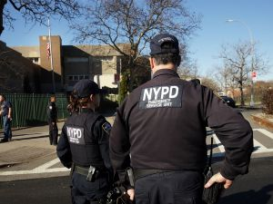"""NEW YORK, NY - DECEMBER 15: New York Police Department officers stand guard in front of the Peter Rouget Brooklyn middle school as children are let back in following reports of a bomb threat on December 15, 2015 in New York City. New York City received the same bomb threat that shut down more than 900 Los Angeles schools on Tuesday. New York Police Commissioner Bill Bratton said the NYPD deemed the threat a """"hoax"""" and has kept schools open. (Photo by Spencer Platt/Getty Images)"""