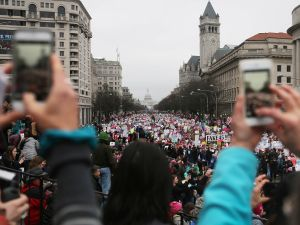 WASHINGTON, DC - JANUARY 21: Women take photos as protesters walk during the Women's March on Washington, with the U.S. Capitol in the background, on January 21, 2017 in Washington, DC. Large crowds are attending the anti-Trump rally a day after U.S. President Donald Trump was sworn in as the 45th U.S. president.