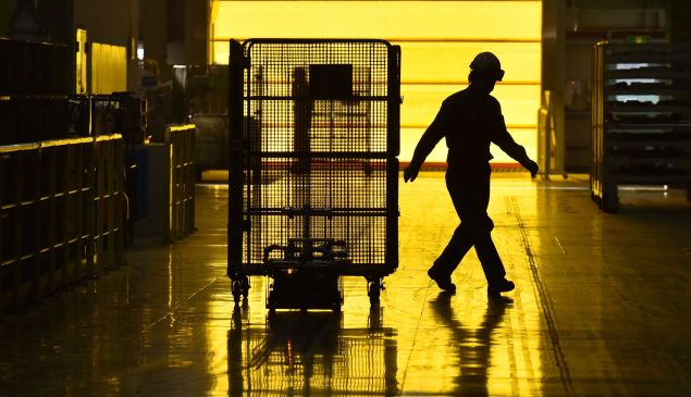 A worker walks past a robot at a recycling factory.