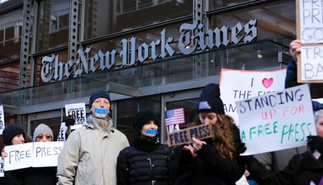 """People take part in a protest outside the New York Times on February 26, 2017 in New York. The White House denied access Frebuary 24. 2017 to an off-camera briefing to several major US media outlets, including CNN and The New York Times. Smaller outlets that have provided favorable coverage however were allowed to attend the briefing by spokesman Sean Spicer. The WHCA said it was """"protesting strongly"""" against the decision to selectively deny media access. The New York Times said the decision was """"an unmistakable insult to democratic ideals,"""" CNN called it """"an unacceptable development,"""" and The Los Angeles Times warned the incident had """"ratcheted up the White House's war on the free press"""" to a new level. / AFP / KENA BETANCUR (Photo credit should read KENA BETANCUR/AFP/Getty Images)"""