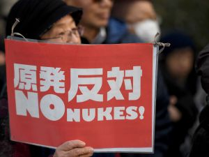 Holding a banner, a protester joins a demonstration in front of the parliament building in Tokyo on March 11, 2017, the sixth anniversary day of the a deadly earthquake, tsunami and nuclear disaster.