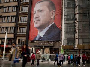 ISTANBUL, TURKEY - MARCH 13: People walk past a large banner showing the portrait of Turkish President Recep Tayyip Erdogan in Taksim Square on March 13, 2017 in Istanbul, Turkey. Turkey will hold its constitutional referendum on April 16, 2017. Turks will vote on 18 proposed amendments to the Constitution of Turkey. The controversial changes seek to replace the parliamentary system and move to a presidential system which would give President Recep Tayyip Erdogan executive authority. Campaigning will officially begin on February 25 with a pro referendum rally to be held in Ankara and attended by Prime Minister Binali Yildirim.