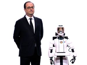 French President Francois Hollande stands beside Leenby, the Cybedroid's latest creation and 5th generation robot.