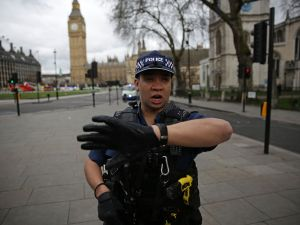 "An armed police officer gestures as he stands guard in Parliament Square, opposite the Houses of Parliament in central London on March 22, 2017 during an emergency incident. British police shot a suspected attacker outside the Houses of Parliament in London on Wednesday after an officer was stabbed in what police said was a ""terrorist"" incident. / AFP PHOTO / DANIEL LEAL-OLIVAS"