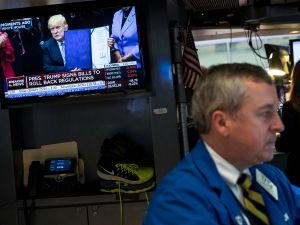 NEW YORK, NY - MARCH 27: A trader works at his desk while a television monitor shows President Donald Trump after he signed four bills that reverse Obama-era regulations and rules on education, land use and federal purchasing, on the floor of the New York Stock Exchange (NYSE), March 27, 2017 in New York City. Today marked the eighth session in a row of decline for the Dow and matched its longest losing streak since 2011.
