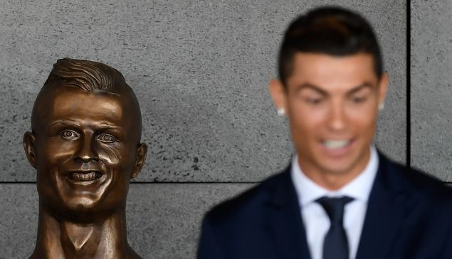"Portuguese footballer Cristiano Ronaldo stands beside a bust presented during a ceremony to rename Madeira's airport in Funchal as ""Cristiano Ronaldo"", on Madeira island, on March 29, 2017. Airport of Madeira, the birthplace of Portuguese footballer Cristiano Ronaldo, was renamed today in honor of the quadruple Ballon d'or and captain of the Portuguese team sacred European champion last summer."