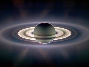 Saturn and its rings backlit by the sun, which is blocked by the planet in this view. Encircling the planet and inner rings is the much more extended E-ring.