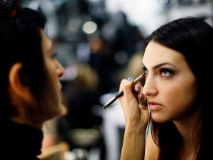A student gets her makeup done at TEEN VOGUE'S Fashion University H&M Shopping Party in New York City.