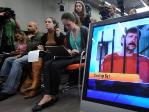 Journalists sit near a screen displaying convicted Russian arms smuggler Viktor Bout in Moscow, on April 12, 2012, during a teleconference with Bout from his US prison. The unusual teleconference involved a video link between Moscow and a New York City studio from which Bout's wife Alla and lawyers arranged a direct five-minute phone conversation with the convicted arms smuggler in his Brooklyn prison. AFP PHOTO/KIRILL KUDRYAVTSEV