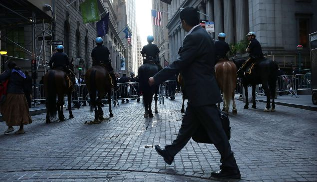 A businessman walks by a police blockade along Wall Street during 'Occupy Wall Street' demonstrations on September 17, 2012.