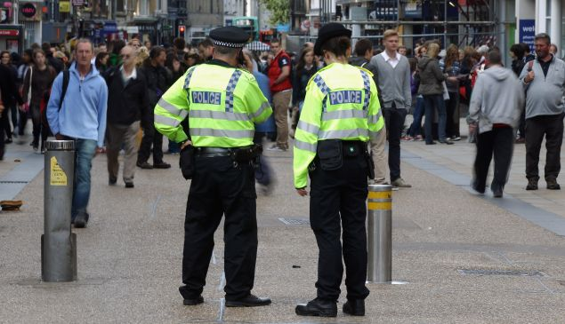 Unarmed police officers patrol the pedestrianized section of Oxford city centre in Oxford, England.