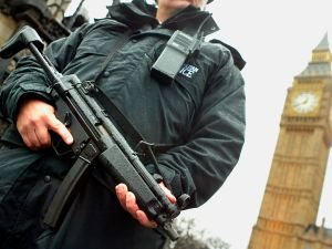 An armed British police officer stands guard outside the Houses of Parliament.