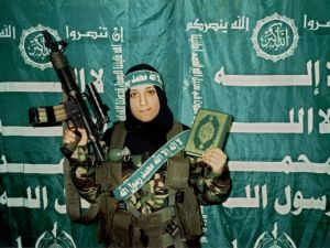 In this undated handout image, Reem Slaleh Raiyshi, a mother of two children from Gaza stands holding a weapon and the Quran holy book.