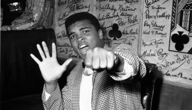 American boxer Cassius Clay holds up five fingers in a prediction of how many rounds it will take him to knock out British boxer Henry Cooper on May 27, 1963.