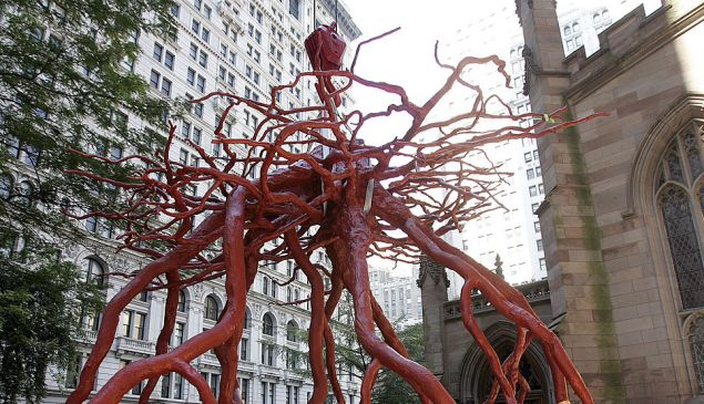 """The """"Trinity Root"""" sculpture is lowered into place by a crane in the Trinity Church yard September 8, 2005 in New York City."""