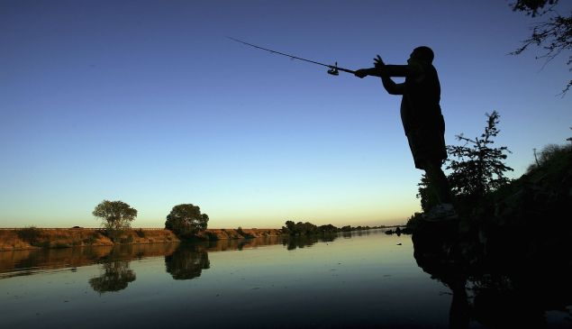 A fisherman casts his line into the Sacramento River south of Sacramento, Calif.