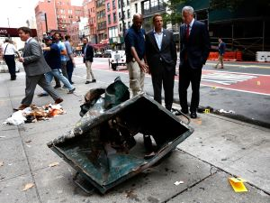 New York Mayor Bill de Blasio (R) and New York Governor Andrew Cuomo (C) stand in front of a mangled dumpster while touring the site of an explosion that occurred on Saturday night on September 18, 2016 in the Chelsea neighborhood of New York City.