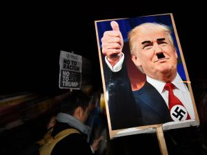 TOPSHOT - A demonstrator holds a placard showing a picture of US President-elect Donald Trump modified to add a swastika and an Adolf Hitler-style moustache during a protest outside the US Embassy in London November 9, 2016 against Trump after he was declared the winner of the US presidential election. Political novice and former reality TV star Donald Trump has defeated Hillary Clinton to take the US presidency, stunning America and the world in an explosive upset fueled by a wave of grassroots anger. / AFP / BEN STANSALL (Photo credit should read BEN STANSALL/AFP/Getty Images)