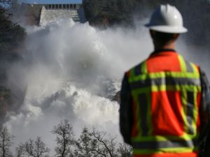 A worker keeps an eye on water coming down the damaged main spillway of the Oroville Dam on February 14, 2017 in Oroville, California.