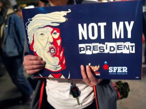"A demonstrator holds an anti-Trump sign during during a President's Day protest march in Denver, Colorado on February 20, 2017. The demonstration was one of many ""Not My President's Day"" anti-Trump marches held throughout the U.S. / AFP /"