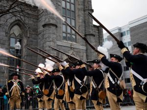 American Revolutionary War reenactors fire musket blanks during the annual St. Patrick's Day parade in South Boston, Massachusetts, on March 19, 2017.