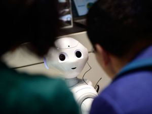 "HANOVER, GERMANY - MARCH 20: The robot ""Pepper"" speaks with visitors at the IBM stand at the CeBIT 2017 Technology Trade Fair on March 20, 2017 in Hanover, Germany. ""Pepper"" has a face detection and is either used to greet Hotel guests during arrival or can be personalized by his owner to help in the household. The 2017 CeBIT will run from March 20-24. (Photo by Alexander Koerner/Getty Images)"