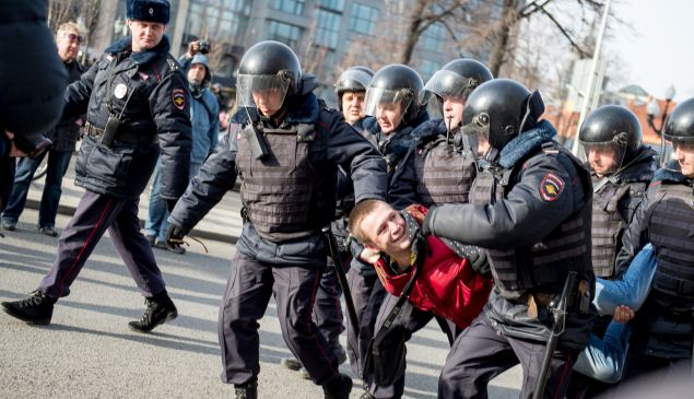 Riot police officers detain a man during an unauthorised anti-corruption rally in central Moscow on March 26, 2017. Thousands of Russians demonstrated across the country on March 26 to protest at corruption, defying bans on rallies which were called by prominent Kremlin critic Alexei Navalny -- who was arrested along with scores of others. Navalny called for the protests after publishing a detailed report this month accusing Prime Minister Dmitry Medvedev of controlling a property empire through a shadowy network of non-profit organisations. / AFP PHOTO / Alexander UTKIN