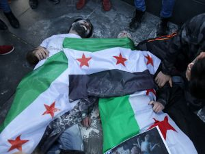 Protesters perform as victims with Syria's former independence flags (which have been adopted by the rebels forces fighting against Syrian pro-government forces in Syria) as they simulate a chemical attack during a demonstration against chemical attacks in Syria on April 6, 2017 on the Place de la Republique, in Paris. An air strike on rebel-held Khan Sheikhun in the northwestern province of Idlib on April 4, 2017 left scores of civilians dead from a suspected chemical weapons attack. At least 86 people -- among them 27 children -- were killed, with results from post-mortems performed on victims pointing to possible exposure to sarin, according to Turkish health officials. / AFP PHOTO / Zakaria ABDELKAFI (Photo credit should read ZAKARIA ABDELKAFI/AFP/Getty Images)