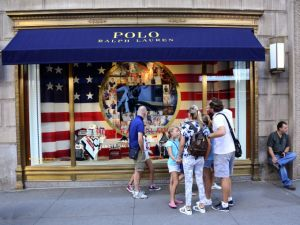 NEW YORK, NY - August 27, 2016: New York City shoppers and visitors pause on their walk along Fifth Avenue to admire the window display at the Polo Ralph Lauren shop on August 27, 2016.