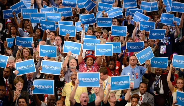 """Supporters hoist signs reading """"Forward"""" in support of then-President Barack Obama."""