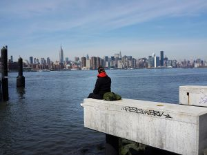 A person sits along open space at the waterfront in Williamsburg, Brooklyn.