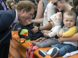 Britain's Prince Harry (L) mimics a baby yawning as he meets the public in Christchurch on May 12, 2015. Prince Harry arrived in New Zealand on May 9 for a week-long visit. AFP PHOTO / POOL / IAIN MCGREGOR (Photo credit should read IAIN MCGREGOR/AFP/Getty Images)