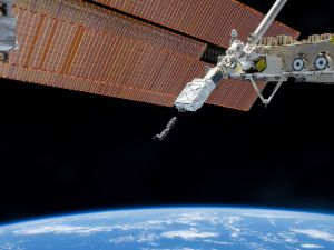The Small Satellite Orbital Deployer (SSOD), in the grasp of the Kibo laboratory robotic arm, deploys a set of NanoRacks CubeSats.