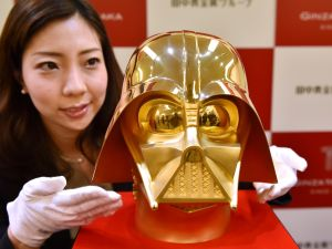 An employee of Japan's jeweler Tanaka Kikinzoku Jewelry displays a pure gold life-size mask of Darth Vader, a character in the Star Wars films, at their main shop in Ginza shopping district in Tokyo on April 25, 2017. In Tokyo's glitzy Ginza, even dark-side Darth Vader goes aureate as a retailer readies to offer the 1.4 million USD golden mask ahead of May 4.