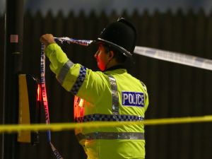 MANCHESTER, ENGLAND - MAY 23: A police officer ties police crime scene tape close to the Manchester Arena on May 23, 2017 in Manchester, England. An explosion occurred at Manchester Arena as concert goers were leaving the venue after Ariana Grande had performed. Greater Manchester Police have confirmed 19 fatalities and at least 50 injured. (Photo by Dave Thompson/Getty Images)