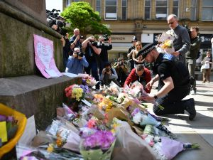 Police officers in front of floral tributes in Manchester, laid as a mark of respect to those in killed and injured following a deadly terror attack at a concert at the Manchester Arena.