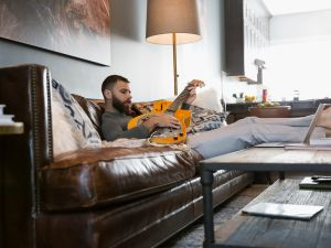 Man playing guitar on living room sofa