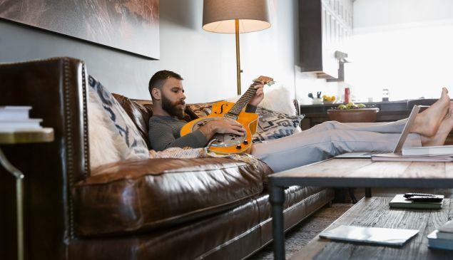 Man playing guitar on living room sofa