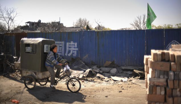 A woman passes through a neighborhood being demolished to make way for new developments in Beijing. Once common, hutongs are becoming a rare sight in the capital.